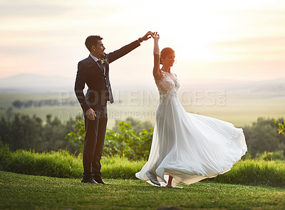 Buy stock photo Shot of a happy young couple dancing outdoors at sunset on their wedding day