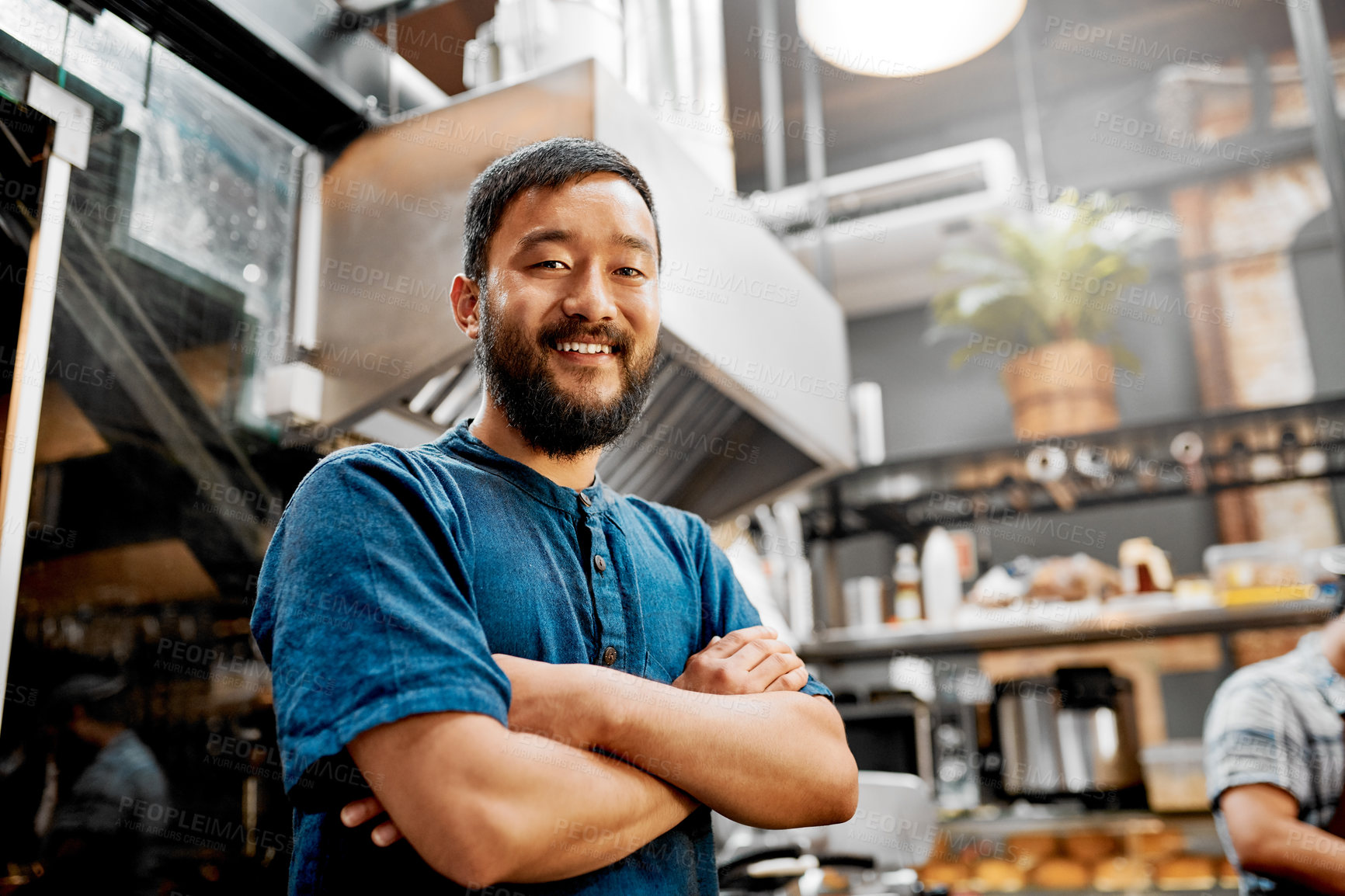 Buy stock photo Portrait of a handsome young barista posing with his arms folded inside a cafe