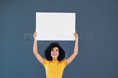 Buy stock photo Studio shot of an attractive young woman holding up a blank placard while standing against a grey background