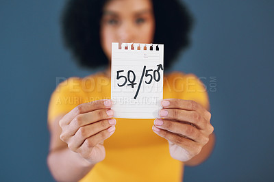 Buy stock photo Studio shot of an unrecognizable young woman holding up a placard with gender symbols on it against a grey background