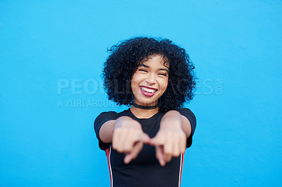 Buy stock photo Portrait of an attractive young woman pointing towards the camera against a blue background
