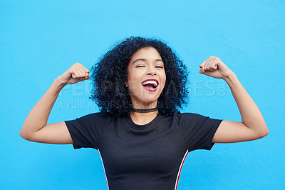 Buy stock photo Portrait of an attractive young flexing her biceps against a blue background