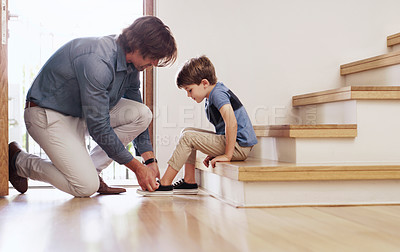 Buy stock photo Full length shot of a father tying his young son's shoelaces at home
