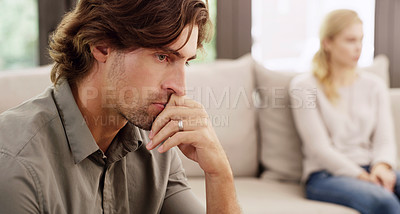 Buy stock photo Shot of a handsome young man looking upset after having a disagreement with his wife at home