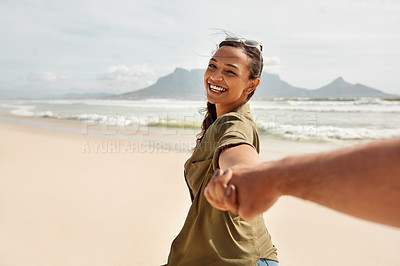 Buy stock photo Shot of a happy young woman leading her boyfriend by the hand at the beach