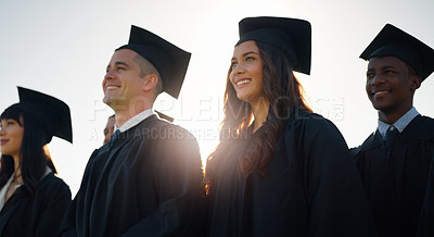 Buy stock photo Cropped shot of a group of cheerful young students standing together on graduation day outside during the day