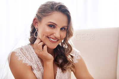 Buy stock photo Cropped portrait of an attractive young bride sitting alone on an armchair in the dressing room before her wedding