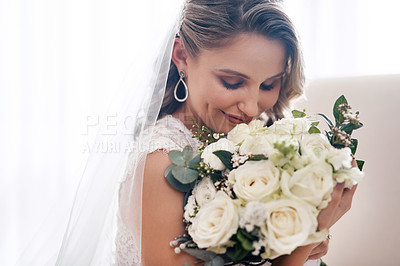 Buy stock photo Cropped shot of an attractive young bride standing in the dressing room alone and smelling her bouquet of flowers