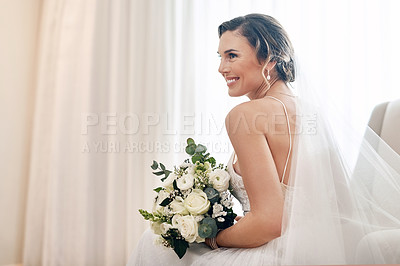 Buy stock photo Cropped shot of an attractive young bride sitting alone in the dressing room and holding her bouquet of flowers