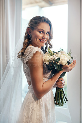 Buy stock photo Cropped portrait of an attractive young bride standing alone in the dressing room and holding her bouquet of flowers