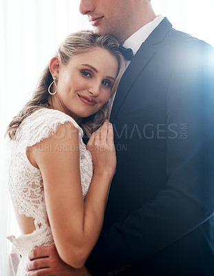Buy stock photo Cropped portrait of an attractive young bride standing indoors and hugging her newlywed husband