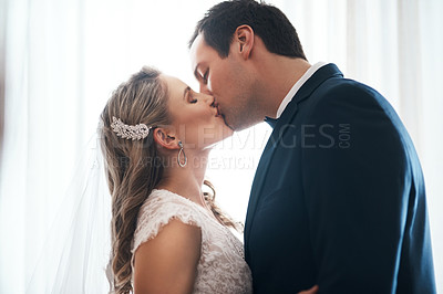 Buy stock photo Cropped shot of an affectionate young couple standing indoors together and kissing after their wedding