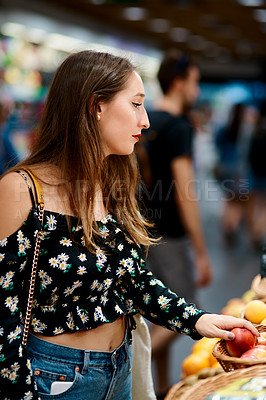 Buy stock photo Cropped shot of an attractive young woman buying fruits at a market in the city