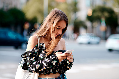 Buy stock photo Cropped shot of an attractive young woman using a smartphone while out in the city