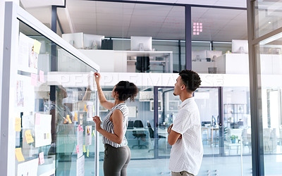 Buy stock photo Shot of two young businesspeople brainstorming ideas and writing notes on a glass wall inside their office