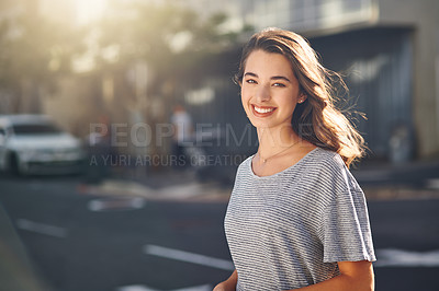 Buy stock photo Cropped portrait of an attractive young woman spending her day out in the city