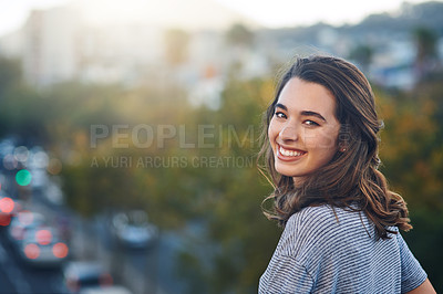 Buy stock photo Rearview portrait of an attractive young woman spending her day out in the city