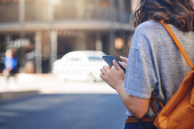 Buy stock photo Rearview shot of an unrecognizable young woman sending text messages while out in the city