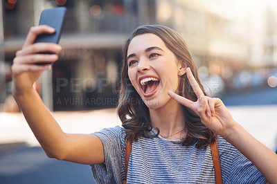 Buy stock photo Cropped shot of an attractive young woman taking selfies while spending her day out in the city