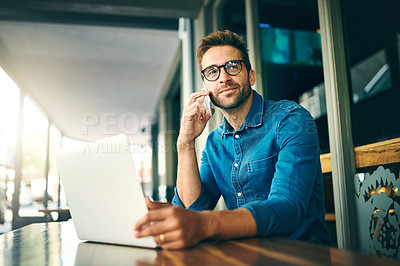 Buy stock photo Cropped shot of a handsome young businessman sitting alone and looking contemplative while using his cellphone in a cafe