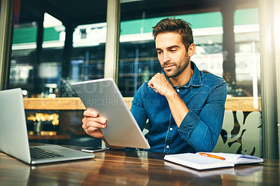 Buy stock photo Cropped shot of a handsome young businessman sitting alone and looking contemplative while using a tablet in a cafe