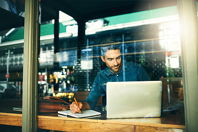Buy stock photo Cropped shot of a handsome young businessman sitting alone and making notes while using his laptop in a cafe
