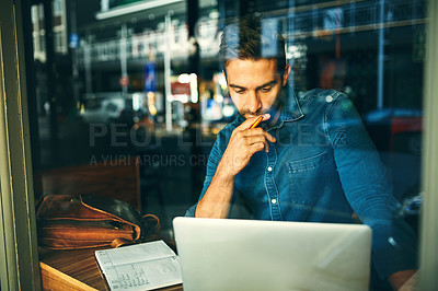 Buy stock photo Cropped shot of a handsome young businessman sitting alone and looking contemplative while using his laptop in a cafe