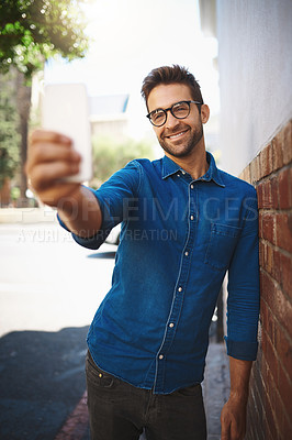Buy stock photo Cropped shot of a man talking on his cellphone while out in the city
