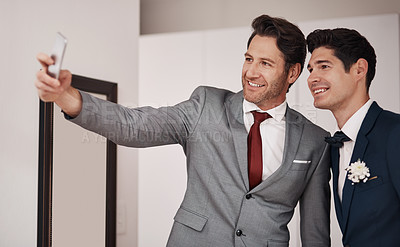 Buy stock photo Cropped shot of a groom and his best man taking a selfie in their dressing room on the wedding day