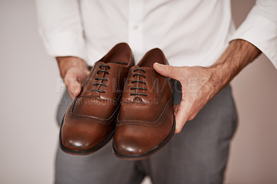 Buy stock photo Cropped shot of an unrecognizable bridegroom holding the shoes he's going to wear in a dressing room