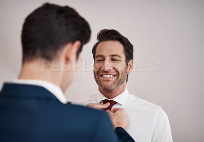 Buy stock photo Cropped shot of a young best man adjusting the groom's tie in a dressing room on the wedding day