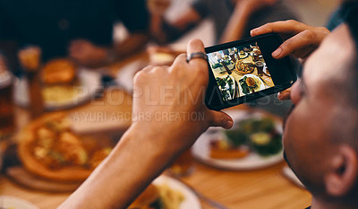 Buy stock photo Shot of a man using his cellphone to take a picture of the pizza on a table