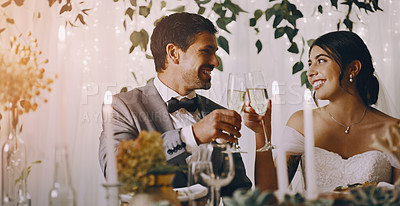 Buy stock photo Cropped shot of an affectionate young newlywed couple sharing a toast while sitting at their wedding reception