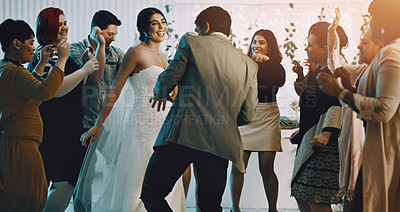 Buy stock photo Cropped shot of an affectionate young newlywed couple dancing alongside their guests on their wedding day