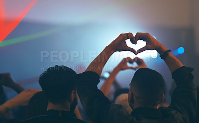 Buy stock photo Rearview shot of a group of unrecognizable young people showing the heart shape while standing in a nightclub