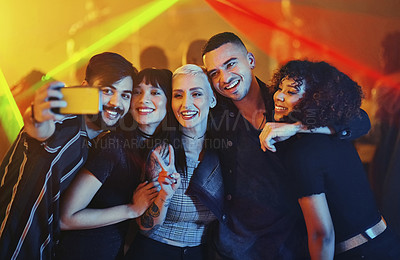 Buy stock photo Cropped shot of a diverse group of young friends taking a selfie at a party in a nightclub