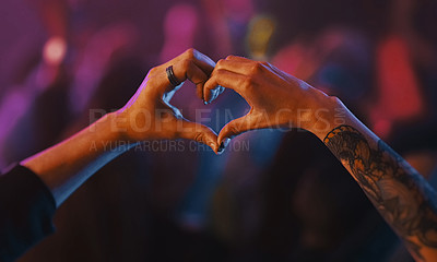 Buy stock photo Cropped shot of an unrecognizable woman's hands making a heart shape at a concert at night