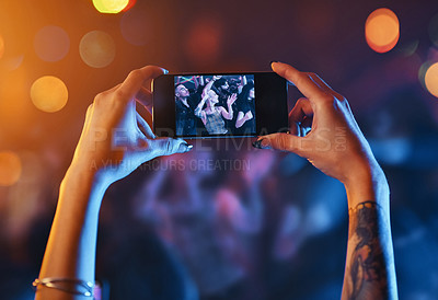 Buy stock photo Cropped shot of an unrecognizable young woman holding up a cameraphone while standing at a concert at night