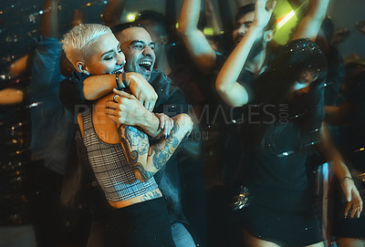 Buy stock photo Cropped shot of an affectionate young couple embracing each other at a party in a nightclub