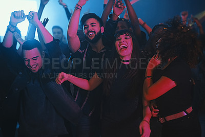 Buy stock photo Cropped shot of a group of energetic young friends dancing at a party in a nightclub