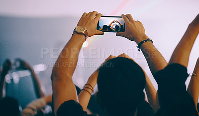 Buy stock photo Rearview shot of an unrecognizable young man holding up a cameraphone while standing at a concert at night