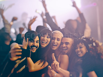 Buy stock photo Cropped shot of a group of energetic young friends taking a selfie at a party in a nightclub