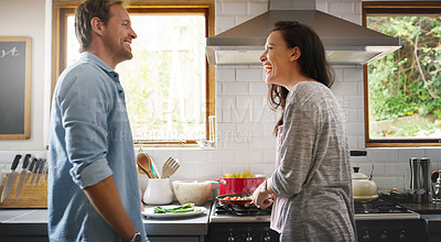 Buy stock photo Cropped shot of an affectionate young woman laughing with her husband while cooking in their kitchen at home