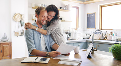 Buy stock photo Cropped shot of an affectionate young woman embracing her husband cheerfully while going through their budget at home