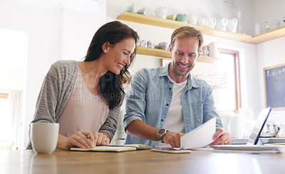 Buy stock photo Cropped shot of an affectionate young man showing his wife some details on a document while going through their budget at home
