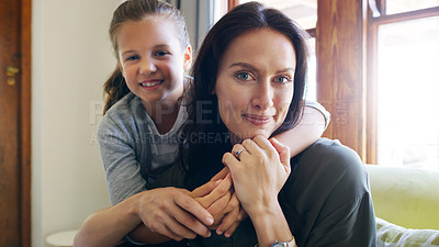 Buy stock photo Cropped portrait of an affectionate young girl embracing her mother in their living room at home