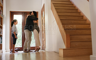 Buy stock photo Full length shot of an affectionate young mother embracing her husband after he arrives home from work