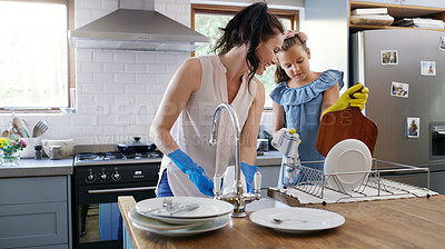Buy stock photo Cropped shot of an affectionate young mother doing the dishes with her daughter in their kitchen at home