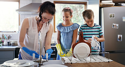 Buy stock photo Cropped shot of an affectionate young mother doing the dishes with her two children in their kitchen at home