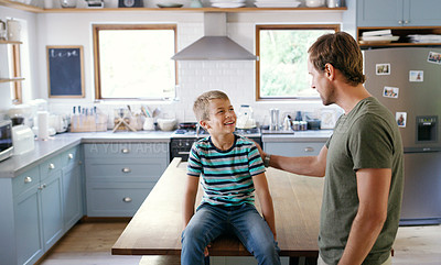 Buy stock photo Cropped shot of an affectionate young boy looking at his father while sitting on the kitchen counter at home